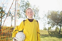 Young female soccer player by net