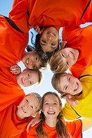 View from below of girls soccer team huddling (thumbnail)