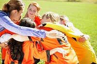 Coach huddling with girls soccer team (thumbnail)
