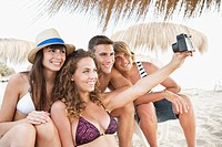 Happy friends on beach taking photo (thumbnail)