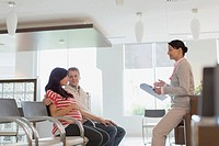 Pregnant couple talking with doctor in waiting room.