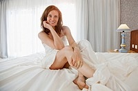 Portrait of mid adult woman sitting on bed