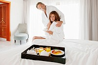 Portrait of couple having breakfast in bedroom