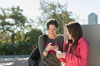 Teenage girls texting on smart phones outdoors