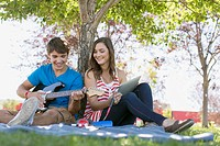 Teenagers relaxing in park with guitar and pc tablet