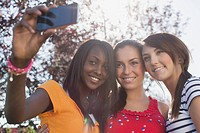 Teenage girls taking self portrait with smart phone (thumbnail)