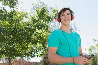 Young adult male in park listening to music