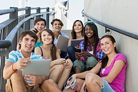 Group of seven teenagers using wireless technology