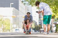 Teens having fun downtown with skateboard.