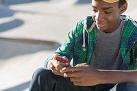African American teenager texting on smart phone.