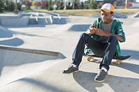 Teenager sitting in skate_park texting on smart phone