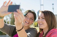 Teenage girls taking self portrait with smart phone.