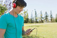 Young adult man listening to music in park
