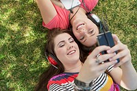 View from above of teenage girls listening to music in park