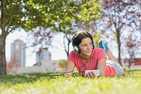 Teenage girl listening to music in city park