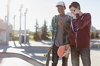 Teenage boys on smart phones at skate_park