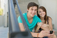 Portrait of young adult couple sitting outdoors on stairway