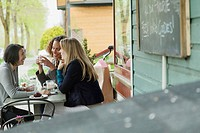 Friends talking at an outdoor cafe (thumbnail)