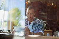 Handsome, African American man using pc tablet in coffee shop (thumbnail)
