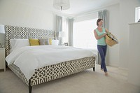 Mid-adult woman with laundry basket in modern bedroom (thumbnail)