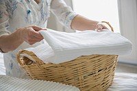 Woman folding towels into wicker basket (thumbnail)