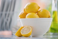 White bowl filled with lemons on counter