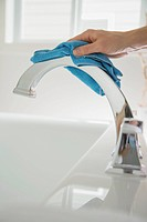 Woman polishing bathroom faucet with cleaning cloth