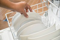 Close_up of woman unloading clean white dishes from dishwasher