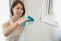 Woman dusting mantle in contemporary home.