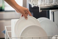 Close_up of woman unloading white dishes from dishwasher