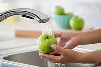 Woman's hands rinsing green apple under kitchen faucet