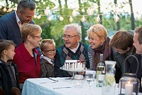 Family gathered around cake at outdoor dinner