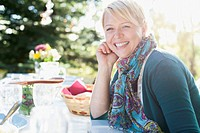 Pretty mid-adult woman smiling while sitting at picnic table