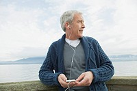 Profile of middle_aged man on dock listening to music