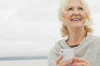Senior woman texting on smartphone by waterfront