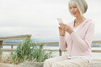 Senior woman texting on smartphone by the beach.