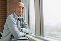 Portrait of senior Asian businessman at window.