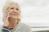 Senior woman on cell phone by waterfront.