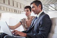 Businessman and businesswoman reviewing work on laptop