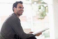 Attractive young businessman in office reading magazine.