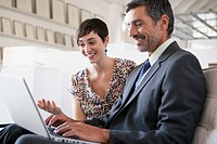 Businessman and businesswoman looking at laptop together
