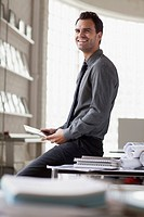 Young architect smiling while sitting on desk.
