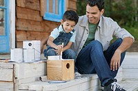 Father and young son painting birdhouse outdoors.