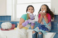 Mother and young daughter blowing dishwater bubbles in kitchen
