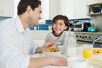 Boy and his dad smiling at each other while they eat cereal