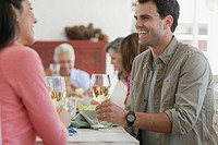 Couple toasting with wine at family dinner table