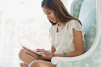 Pretty preteen using pc tablet at home