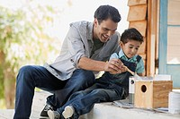 Father and young son painting birdhouse together
