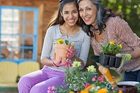Portrait of pretty mother and daughter with flowers to plant