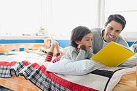 Mid_adult man reading book to young son